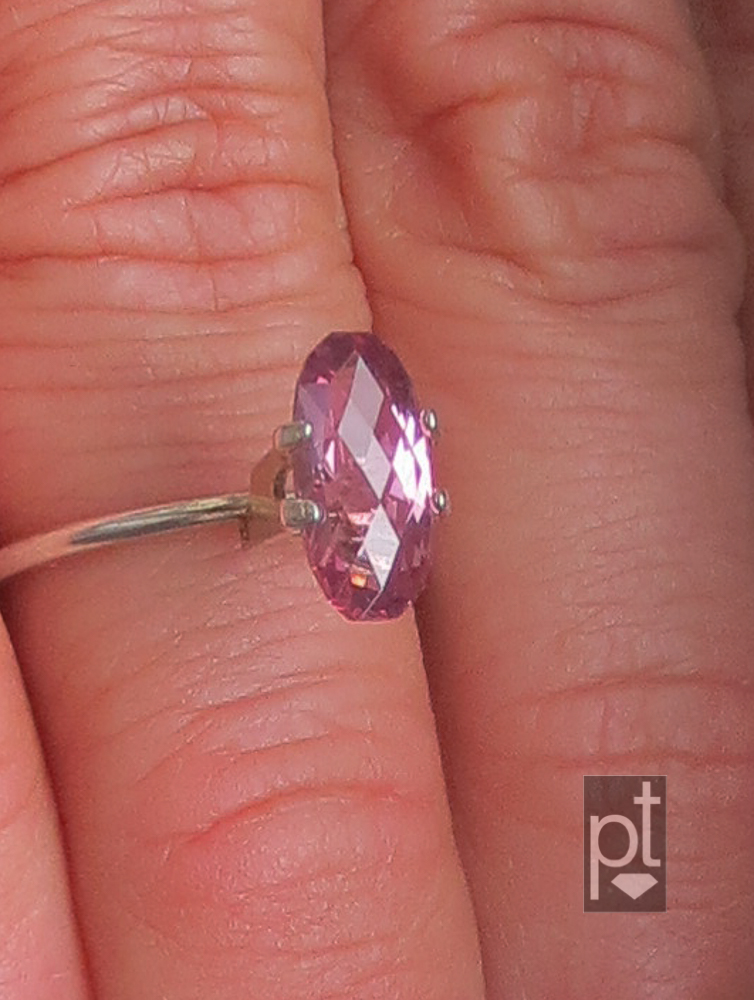 Purple-Pink Spinel in hand, indirect lighting